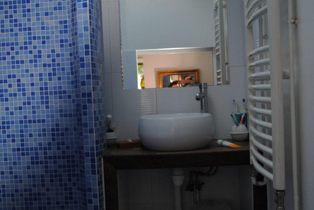 Espace lavabo avec miroir, carrelage mosaïque bleu et porte serviette