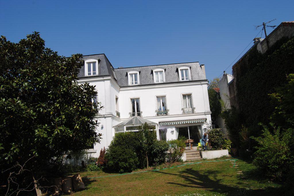 Grande maison de style colonial de deux étages avec façade blanche et tuiles abimées