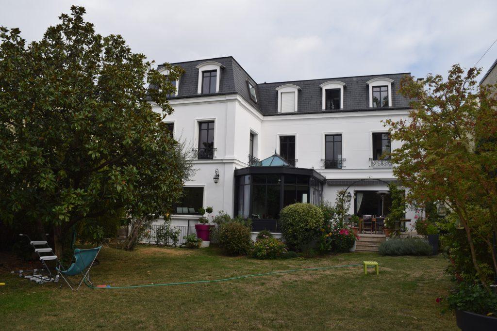 Grande maison de style colonial de deux étages avec façade blanche et jardin bien entretenu