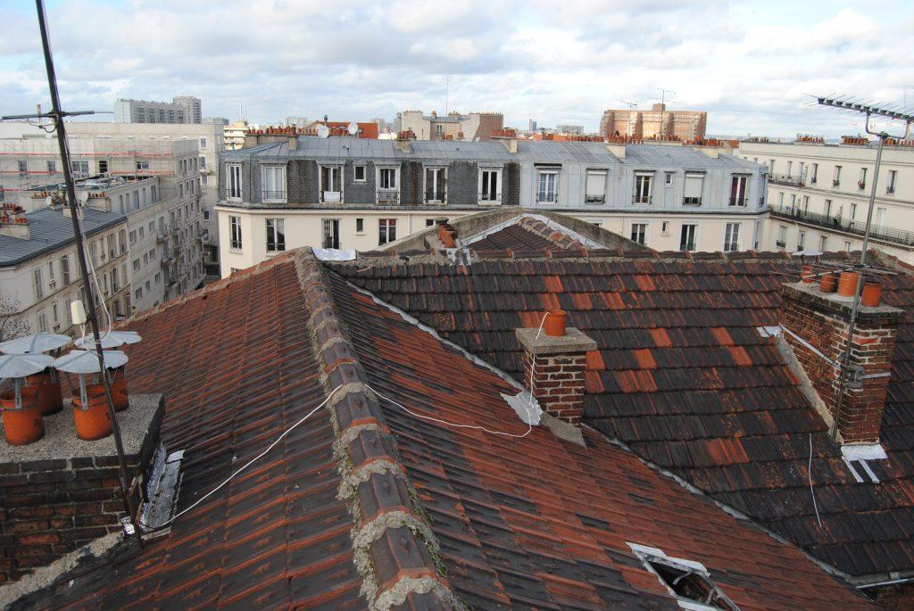 Photo prise en hauteur d'un toit avec tuiles abîmées
