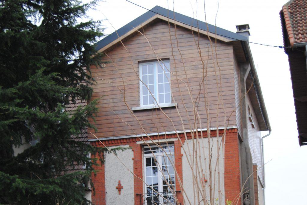 Maison en brique rouge avec une extension en bois extérieur et sortie de toit
