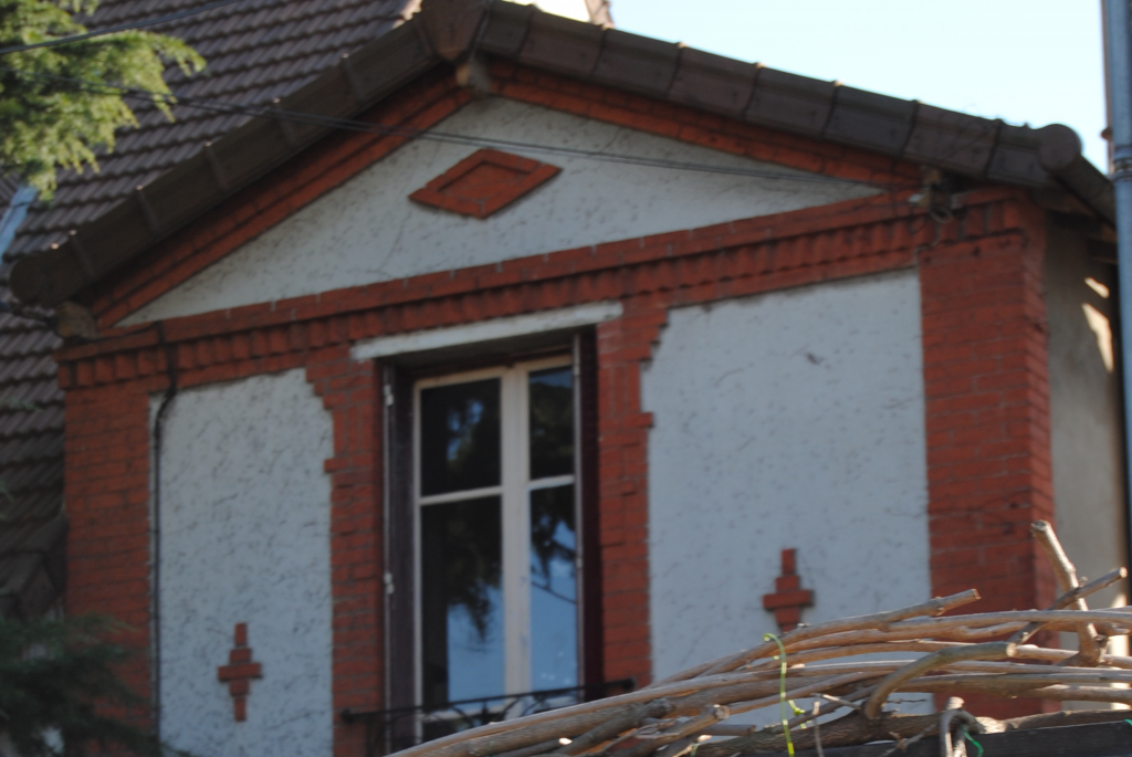 Maison en brique rouge décoratif et toiture en pente avec gouttière de chaque côté