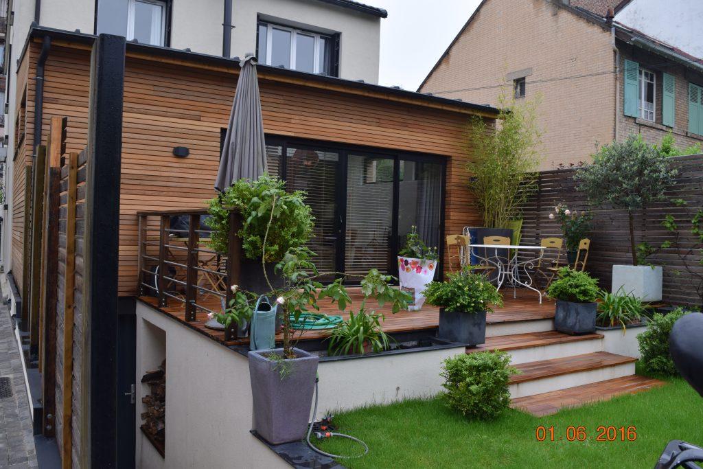 Terrasse en parquet extérieur avec petite table d'extérieur et espace vert