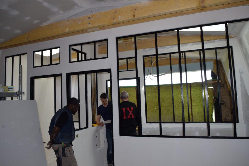 Salle vide en rénovation avec les agents de Toits et Moi travaillant