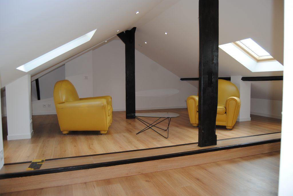 Espace détente avec fauteuils jaune vintage, poutre apparente de couleur sombre et parquet