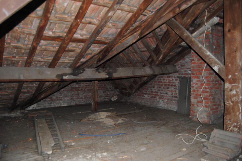 Photo de l'intérieur d'une toiture avec charpente en bois en très mauvais état