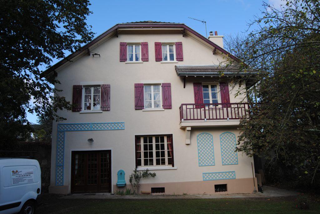 Grande bâtisse de style ancien avec volet rouge et décoration mural bleu turquoise