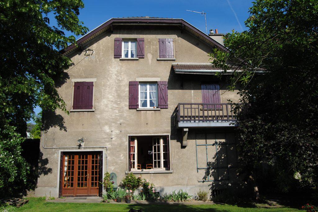 Grande bâtisse de style ancien avec volets et façade abimés