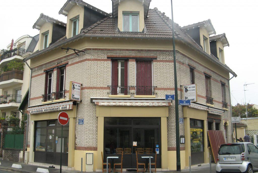Brasserie Restaurant Bar a deux étages avec volets rouge et toit en pente et tuiles marron