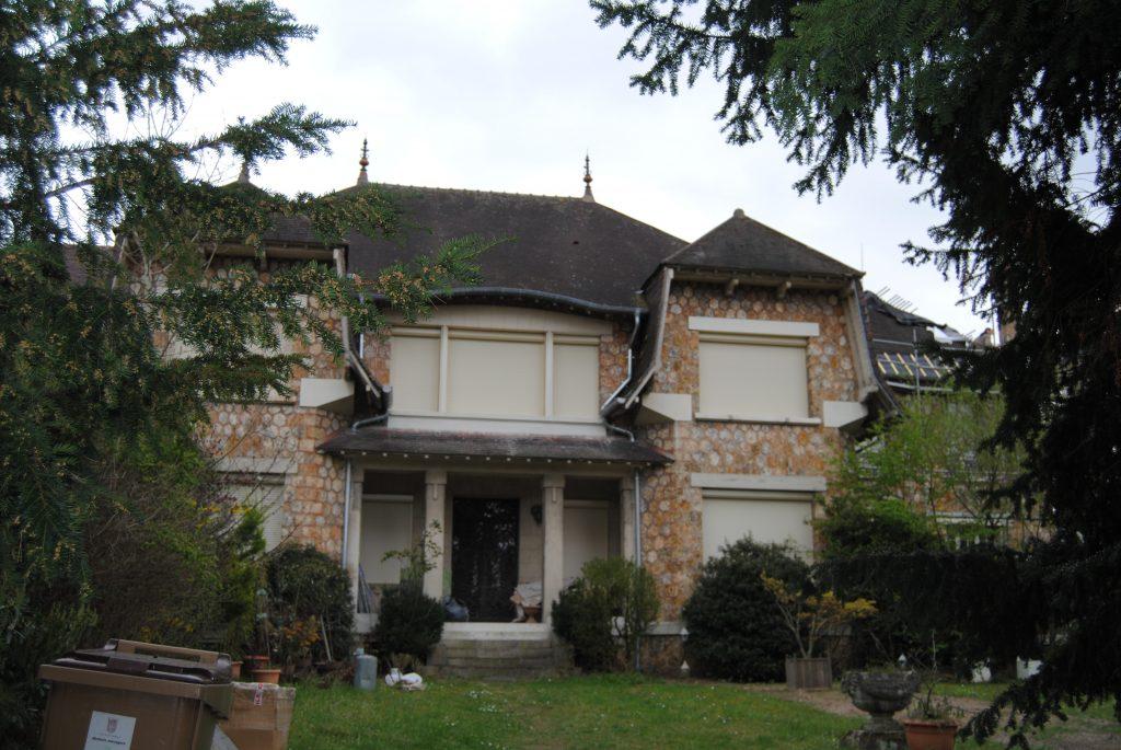 Grande maison avec toits en pente aux tuiles abîmées