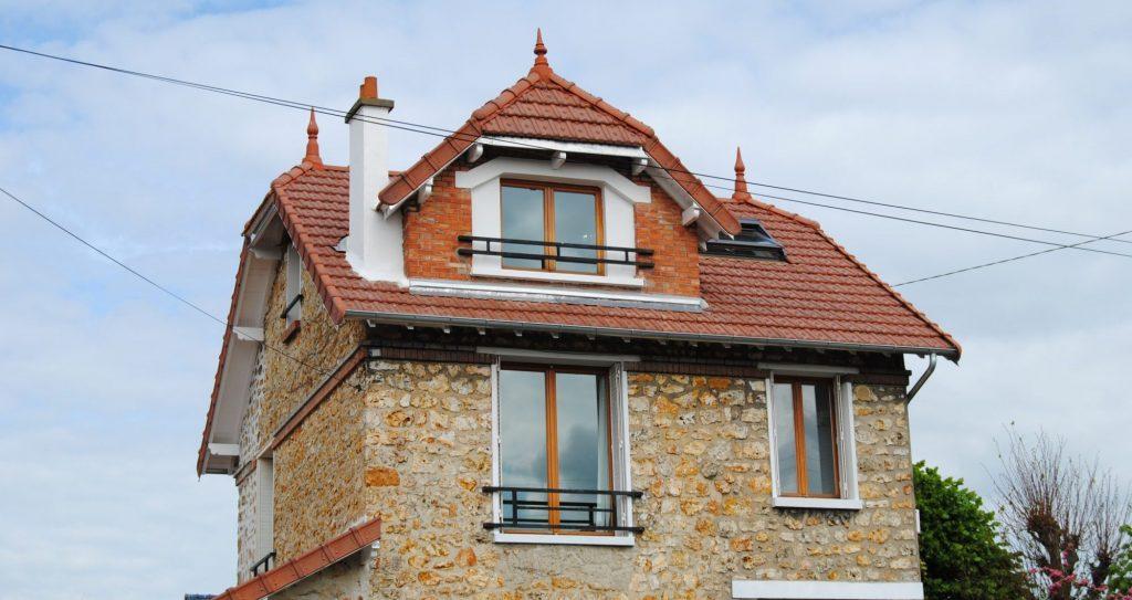Maison original avec toiture en pente en tuiles mécanique rouge avec barrière noir métallique