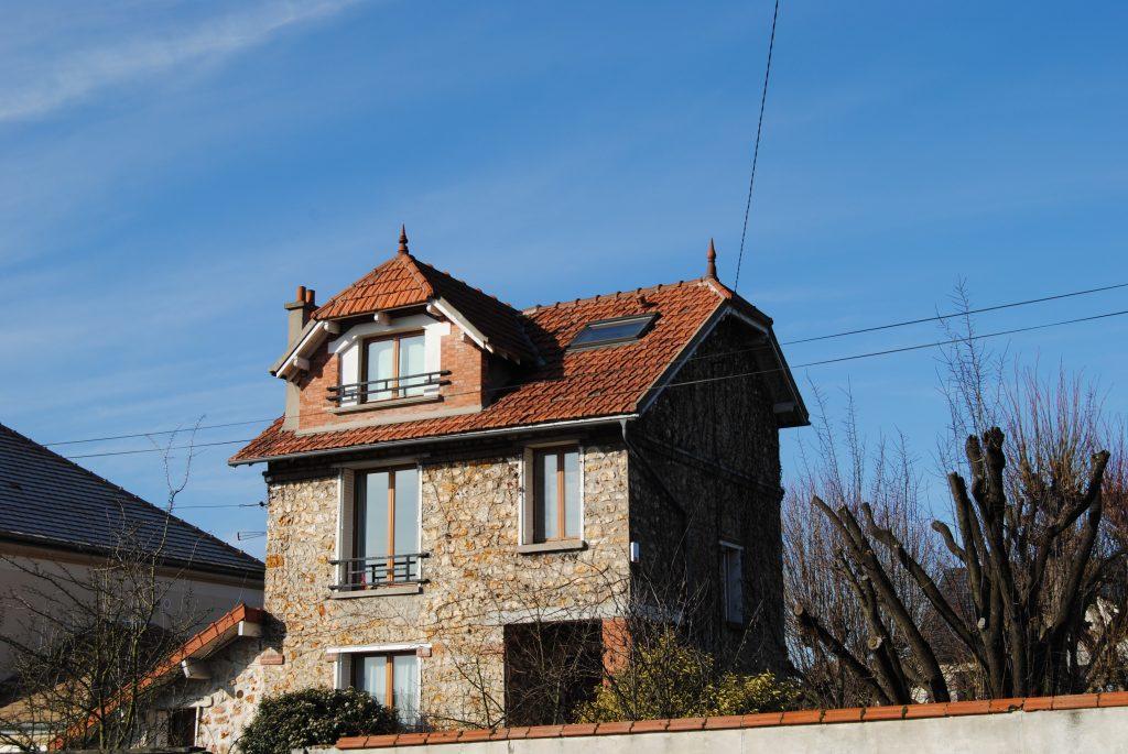 Maison original avec toiture en pente en tuiles mécanique rouge abîmées avec barrière noir métallique