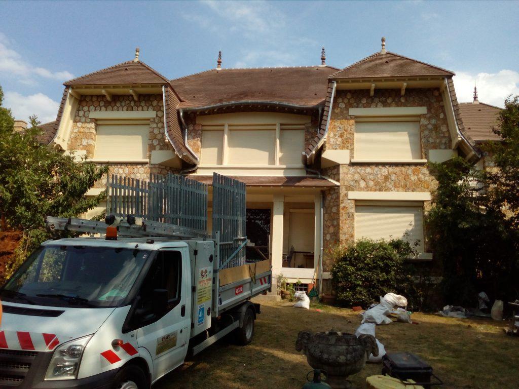Grande maison avec tuiles marron et van de rénovation dans le jardin